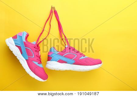 Sport shoes on yellow background, close up