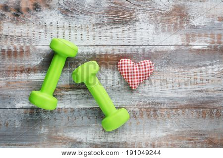 Green Dumbbells With Red Heart On Grey Wooden Table