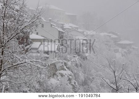 Foggy view of the houses and trees on the hill in the town of Veliko Tarnovo in Bulgaria in the winter