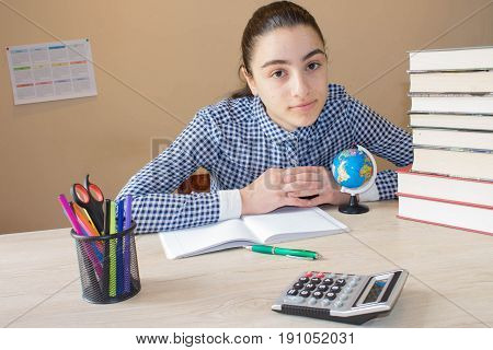 Young girl with thoughtful expression sitting at a desk on some books. Education and school concept - little student girl with many books