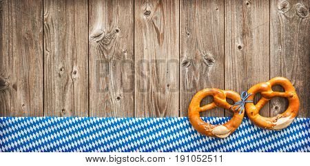 Rustic background for Oktoberfest with Bavarian white and blue fabric and pretzels