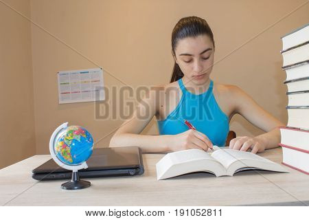Education concept - books on the desk in the auditorium. Beautiful girl doing her homework