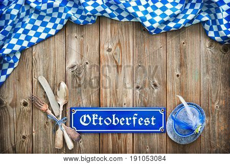 Rustic background for Oktoberfest with Bavarian white and blue fabric, traditional hat and silverware