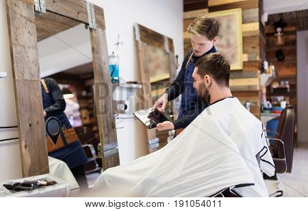 grooming, technology and people concept - hairdresser or barber showing tablet pc computer to man at barbershop