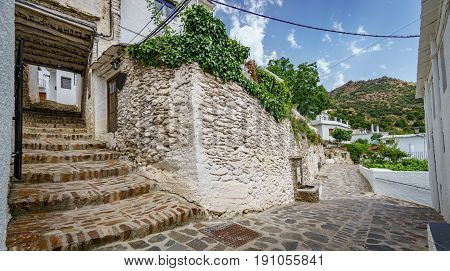 Wide angle view of street and stairs house entrance with plantpots in Capileira, Granada, Spain