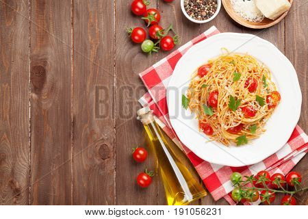 Spaghetti pasta with tomatoes and parsley on wooden table. Top view with copy space