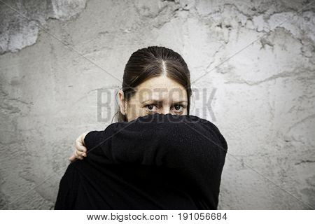 Woman covering her face detail of a young woman with problems gender violence