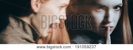 Young woman with schizophrenia with her finger on the mouth