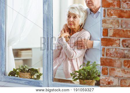 Elderly sad man and woman embraced next to window
