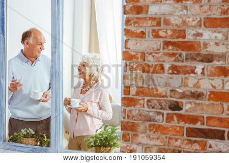 Senior smiling man and woman drinking tea and talking by the window