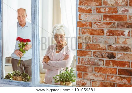 Senior man with flowers apologizing to sad elegant woman