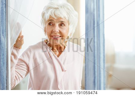 Smiling elegant woman peeping through the window