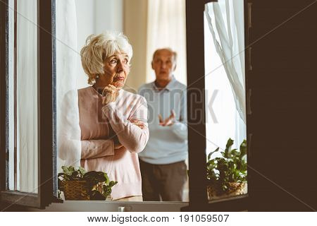 Elderly sad woman giving her husband silent treatment in apartment