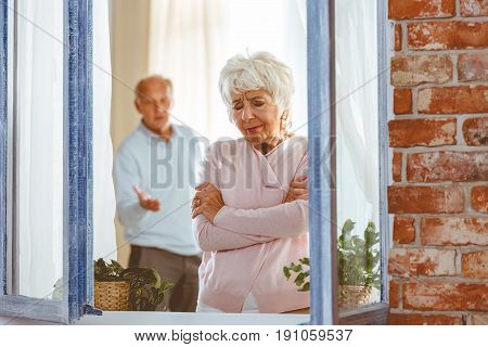 Elderly couple having argument by the window