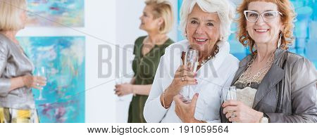 Female senior elegant friends celebrating at art exhibition