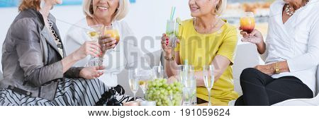 Group of stylish senior women having drinks and smiling in elegant interior