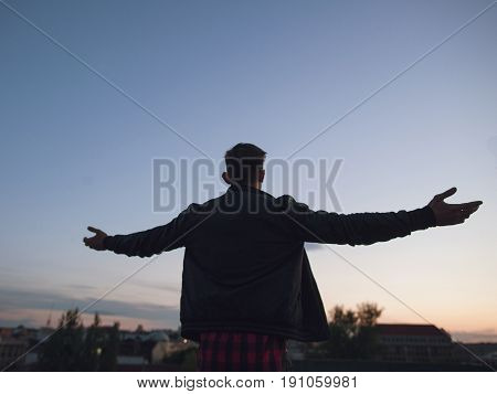 Man on top of the world. Hello world. Young male leader silhouette on blue sky background. New successful business, lonely morning, freedom and liberty in life concept
