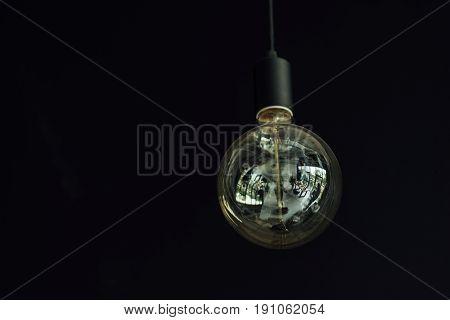 Vintage hanging Edison light bulb on black background