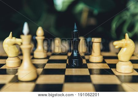 Closeup View Of Black And White Chess Figures On Chess Board. Selective Focus On Black Bishop  Figur