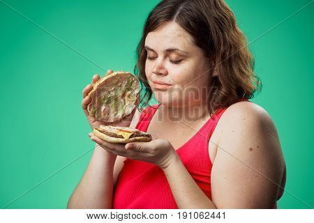 Woman with a hamburger, woman looks at a hamburger on a green background.