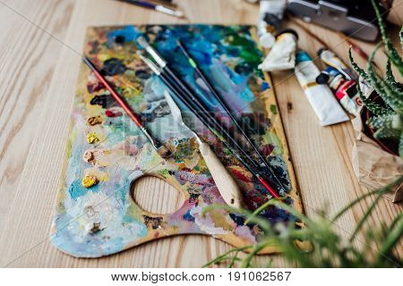 High Angle View Of Artist Palette With Paint Brushes, Palette Knife And Oil Paint Tubes On The Table