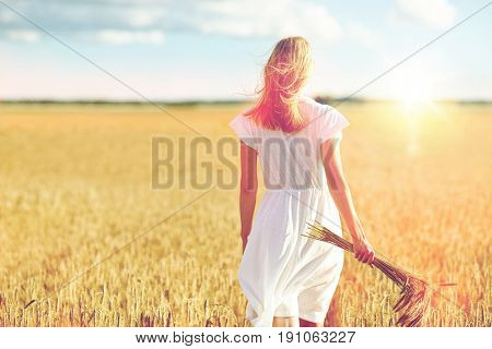 happiness, nature, summer holidays, vacation and people concept - young woman with cereal spikelets walking on field