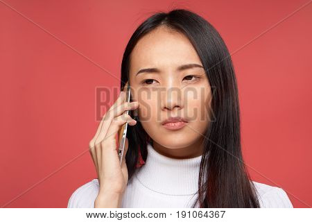 Woman talking on the phone, woman holding the phone near the ear on a red background.