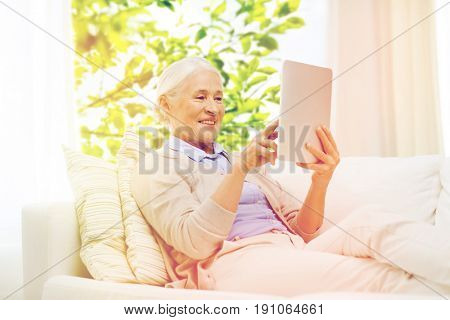 technology, age and people concept - happy senior woman with tablet pc computer at home over window and green natural background