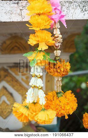 close up marigold garland on spirit House