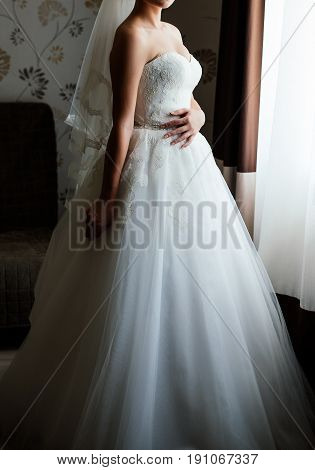 Beautiful Young Bride In White Dress Waiting For The Groom Indoors. Elegant Charming Young Brunette