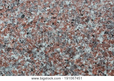 Texture of granite background with black rea white and gray spots.