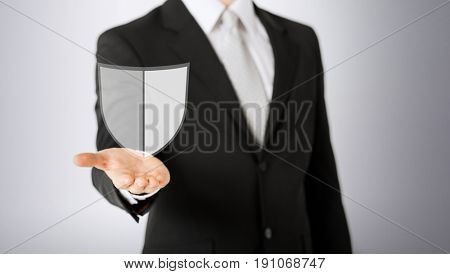 business, people and cyber protection concept - close up of man with virtual antivirus program shield icon over gray background