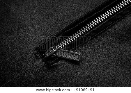 Black zipper and leather texture close up background.