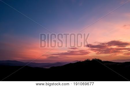 Silhouette Landscape Under Sunset Sky In Spring With Clouds In The Background, Spring Time At Dusk