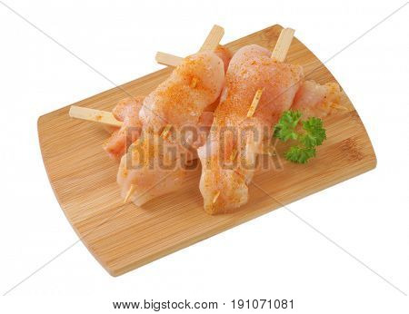 raw chicken skewers on wooden cutting board