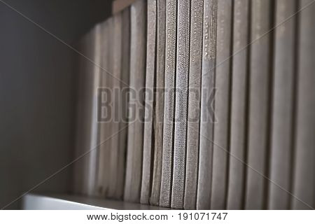 Old books on wooden shelf. No readable labels.