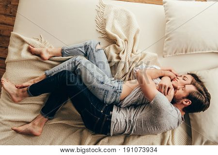 High Angle View Of Beautiful Happy Young Couple Hugging While Sleeping On Bed