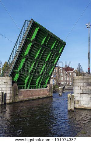 Green drawbridge in the day in Amsterdam