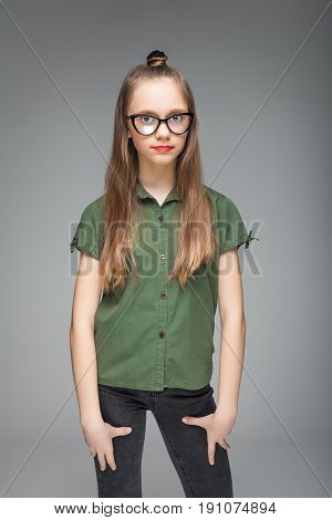 young beautiful brunette spectacled girl over gray background. woman dressed in green T-shirt and black jeans. red lips.