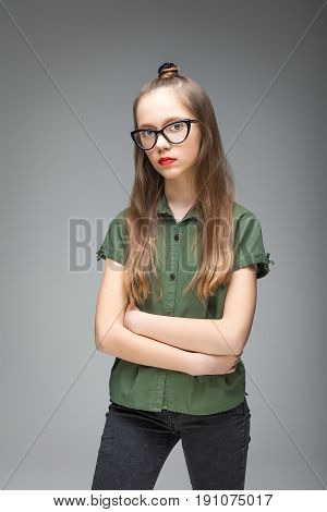Portrait of young brunette spectacled girl over gray background. woman dressed in green T-shirt and black jeans. red lips.
