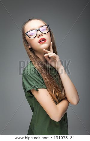 young brunette cute spectacled girl over gray background. woman dressed in green T-shirt and black jeans. red lips.