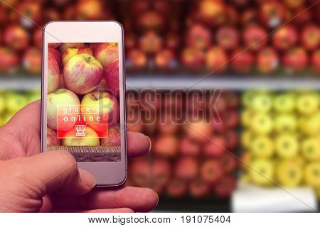 hand holding mobile with grocery online text with blur fruits in supermarket background