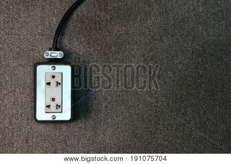 electrical outlet plug with cable on carpet floor