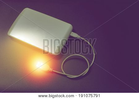 white external hard drive and red spot like data for backup on black background