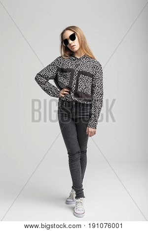 Portrait of young cute girl with black sunglasses over gray background. woman dressed in black T-shirt, black jeans and white shoe