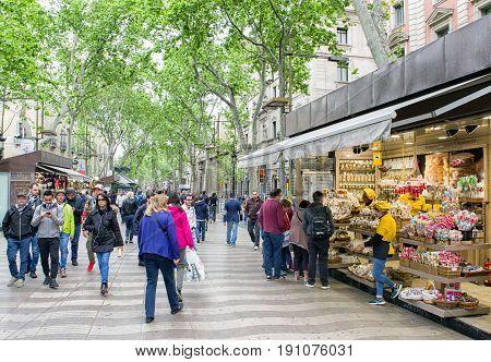 BARCELONA SPAIN - APRIL 19: Crowded famous street La Rambla on April 19 2017 in Barcelona