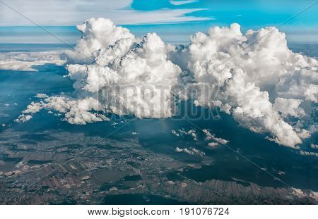 Views of clouds and land from airplane window from a height. The horizontal frame.