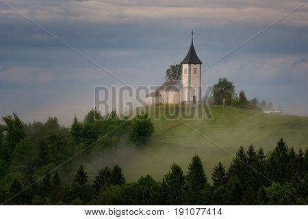 Jamnik church on a hillside in the spring, foggy weather at sunset in Slovenia, Europe. Mountain landscape shortly after spring rain. Slovenian Alps.