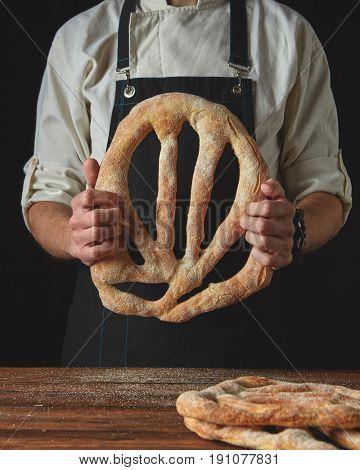 Baker's hands hold fougas bread