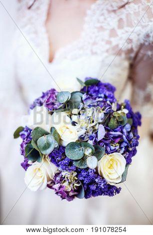 Beautiful purple wedding bouquet in hands. The bride's bouquet.